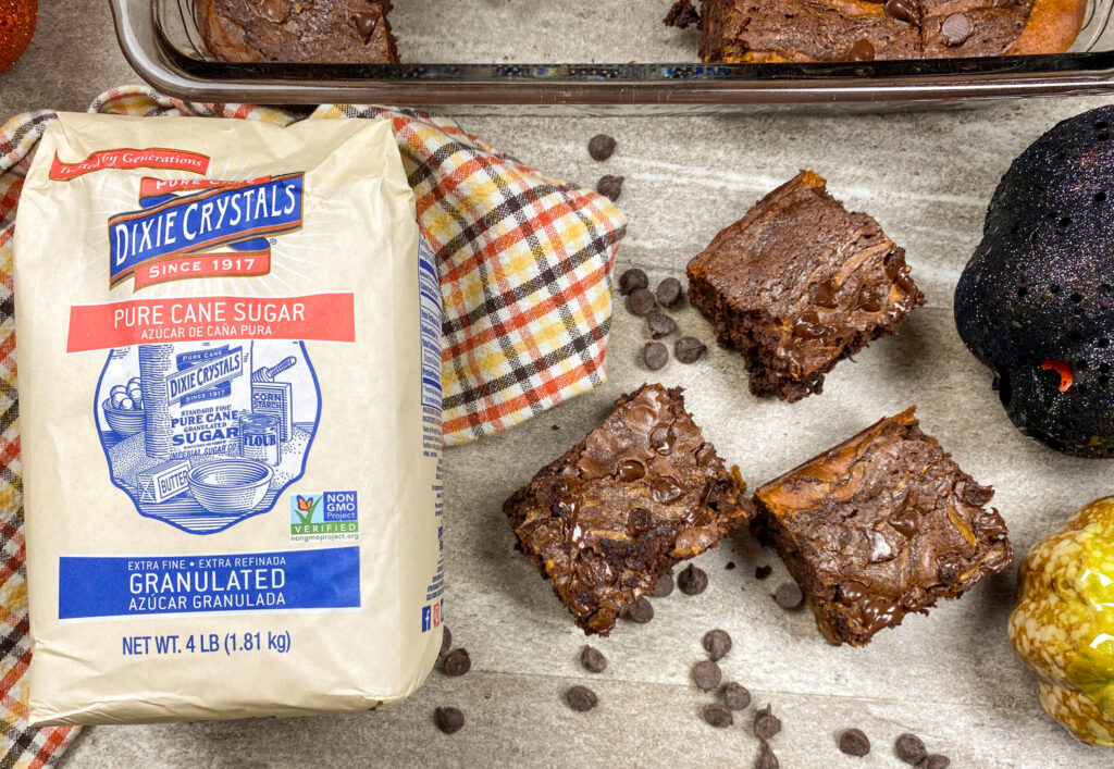 Brownies sitting on the counter with a bag of Dixie Crystals sugar.