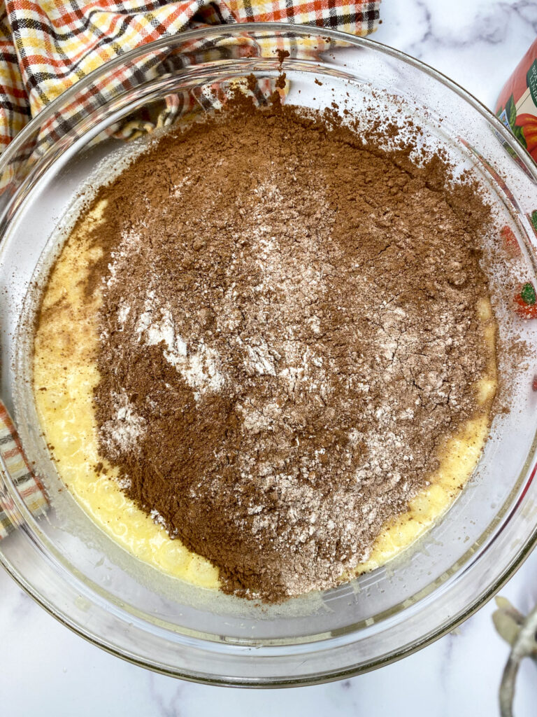 Sifted flour being added to a bowl with eggs and sugar.