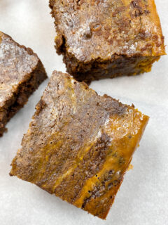Three brownies sitting on parchment paper.