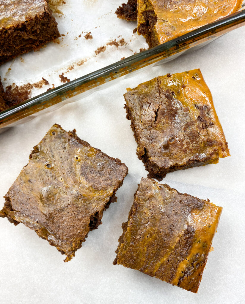 Three pumpkin chocolate brownies on parchment paper.
