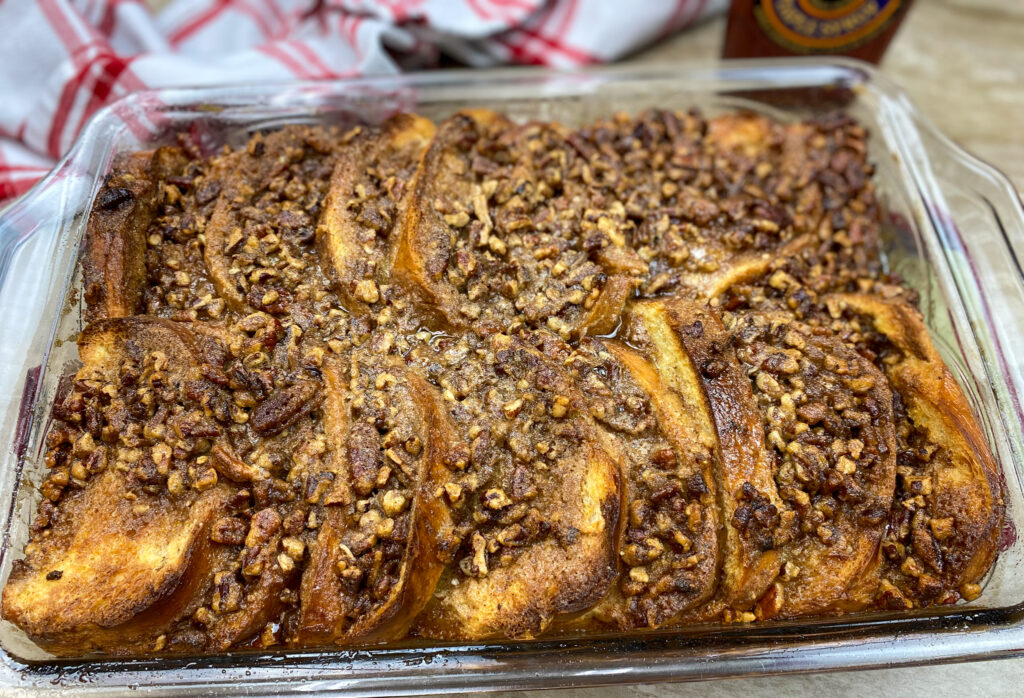 French toast casserole baked in a casserole dish with pecans on top.