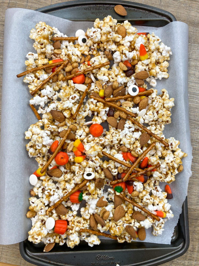 Popcorn with candy, pretzels, peanuts, and almonds spread out on a cookie sheet covered in parchment paper.