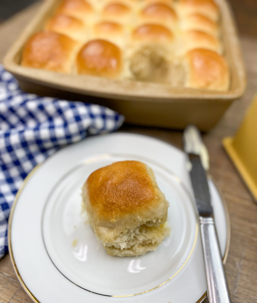 Homemade dinner rolls in a pan and on a white plate.