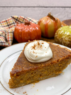 A slice of sweet potato pie on a plate with whipped topping.
