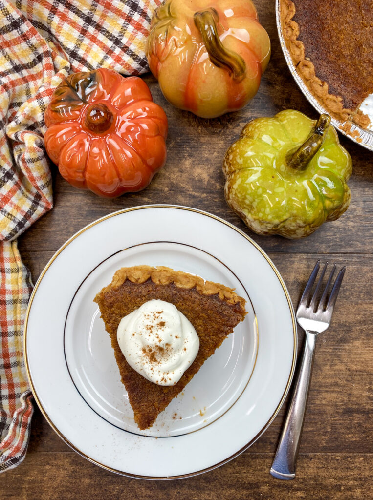 A slice of sweet potato pie on a white plate with whipped cream on top.