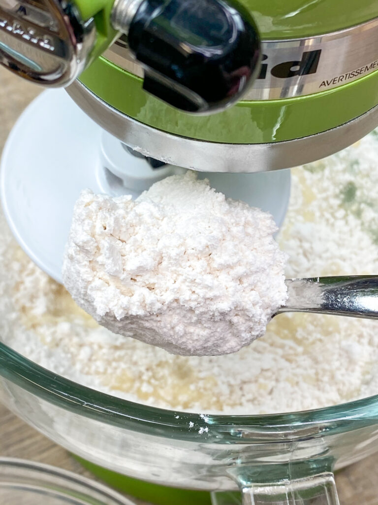 Adding flour to a glass bowl for homemade yeast rolls.