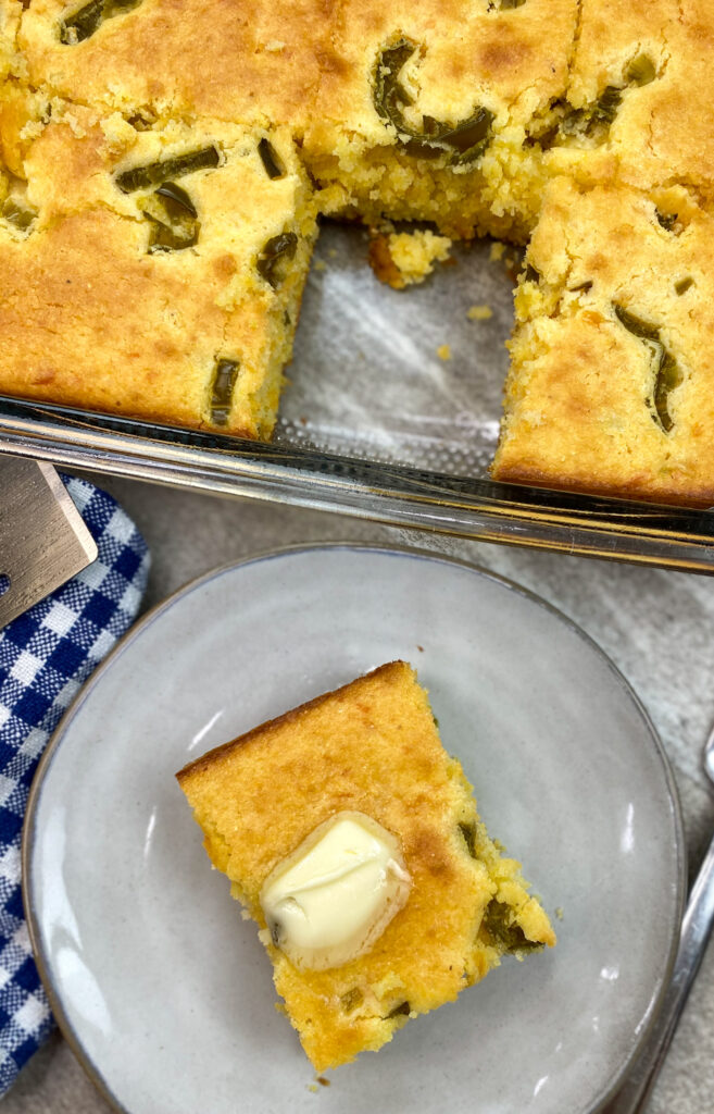 Easy Jiffy jalapeño cornbread on a plate with butter on top.