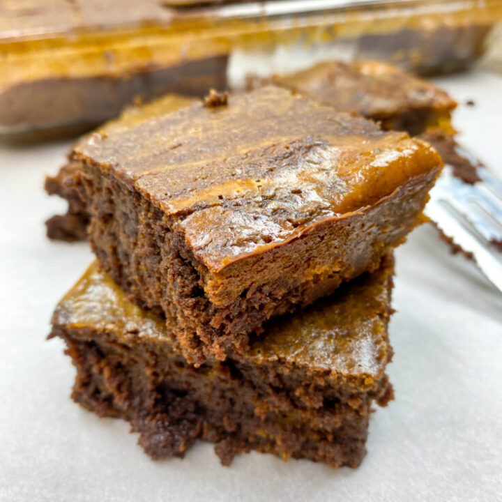 Pumpkin brownies stacked oh top of each other.