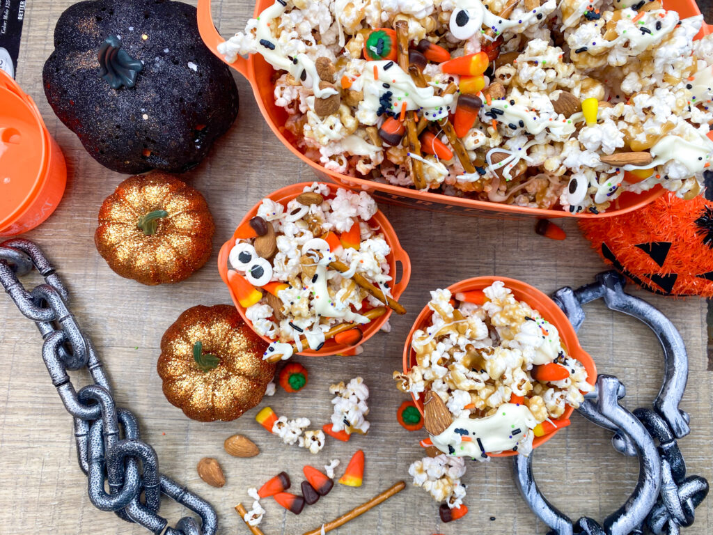 Caramel popcorn with candy corn, pretzels, and peanuts in orange containers.