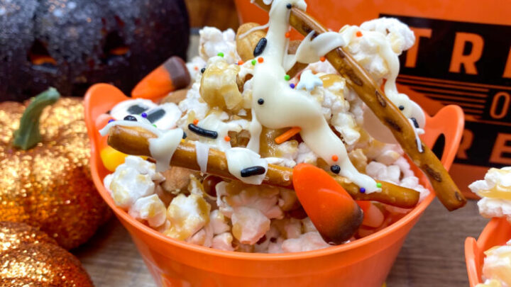 Halloween caramel popcorn in an orange cup with Trick-Or-Treat written on the outside.