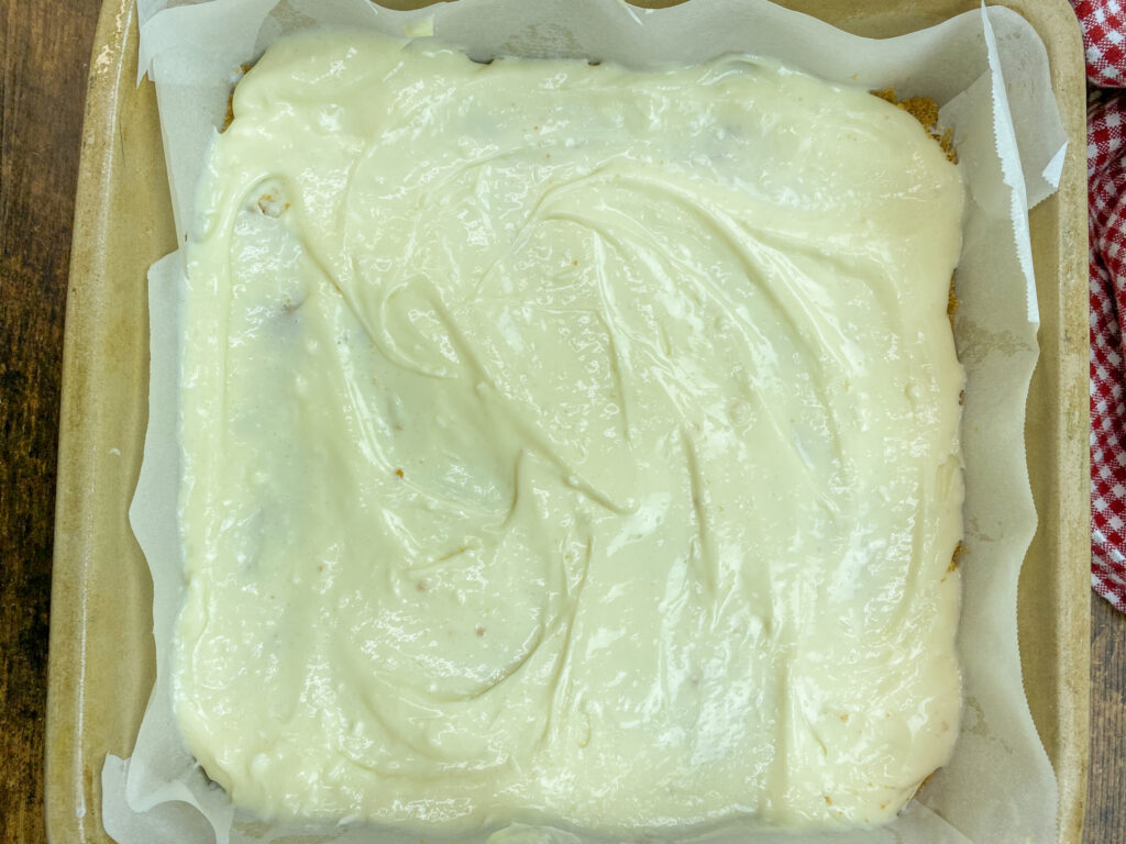 Cream cheese filling spread into a square baking dish.