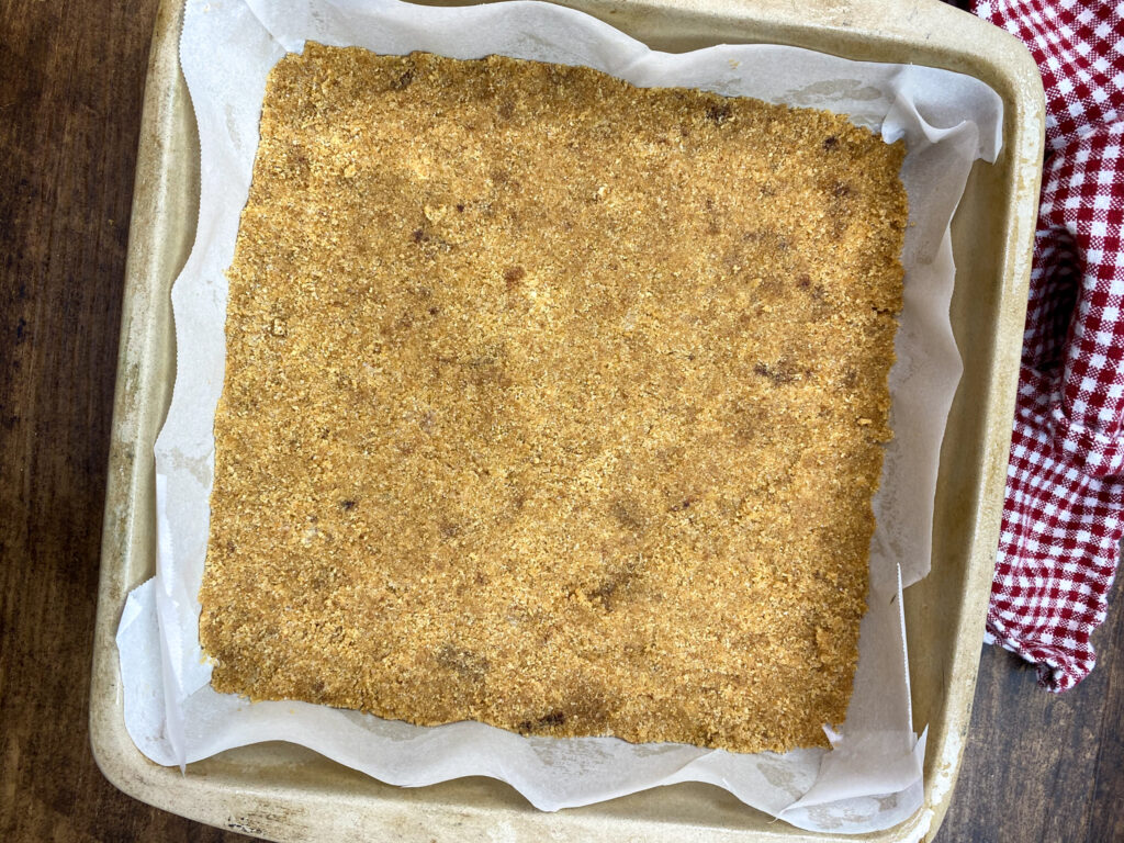 A graham cracker crust in a square baking dish.