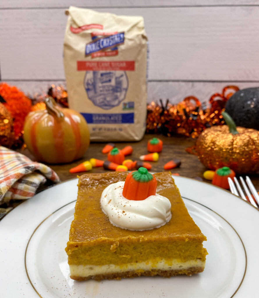 A pumpkin cheesecake bar on a white plate surrounded by fall decorations.