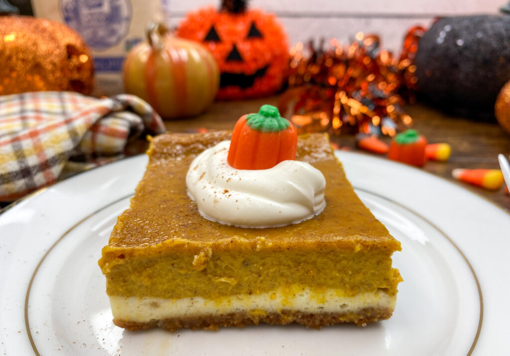 A pumpkin cheesecake bar on a white plate with whipped cream and a candy pumpkin on top.