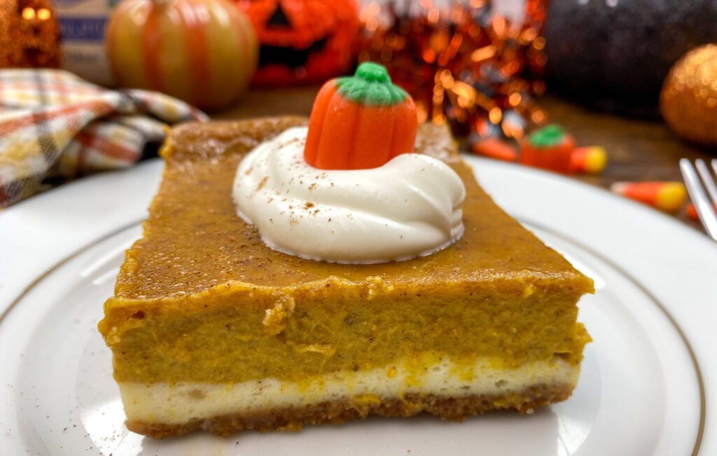 Pumpkin pie bar on a white plate with a candy corn pumpkin on top of whipped cream.