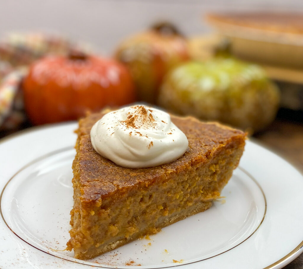 A slice of pie on a white plate with ceramic pumpkins in the background.