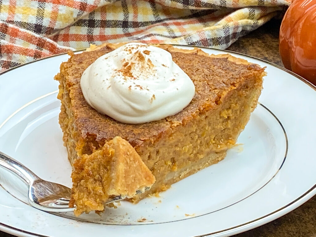 A slice of Southern sweet potato pie on a white plate with a fork.