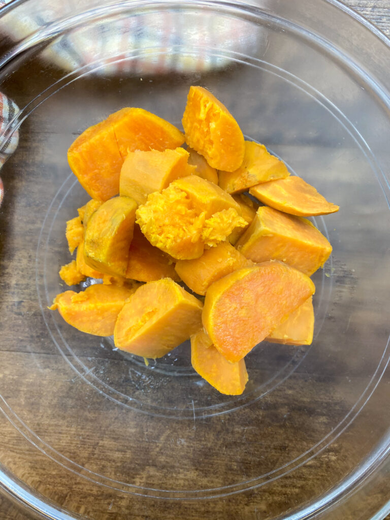 Cooked sweet potatoes in a glass bowl.