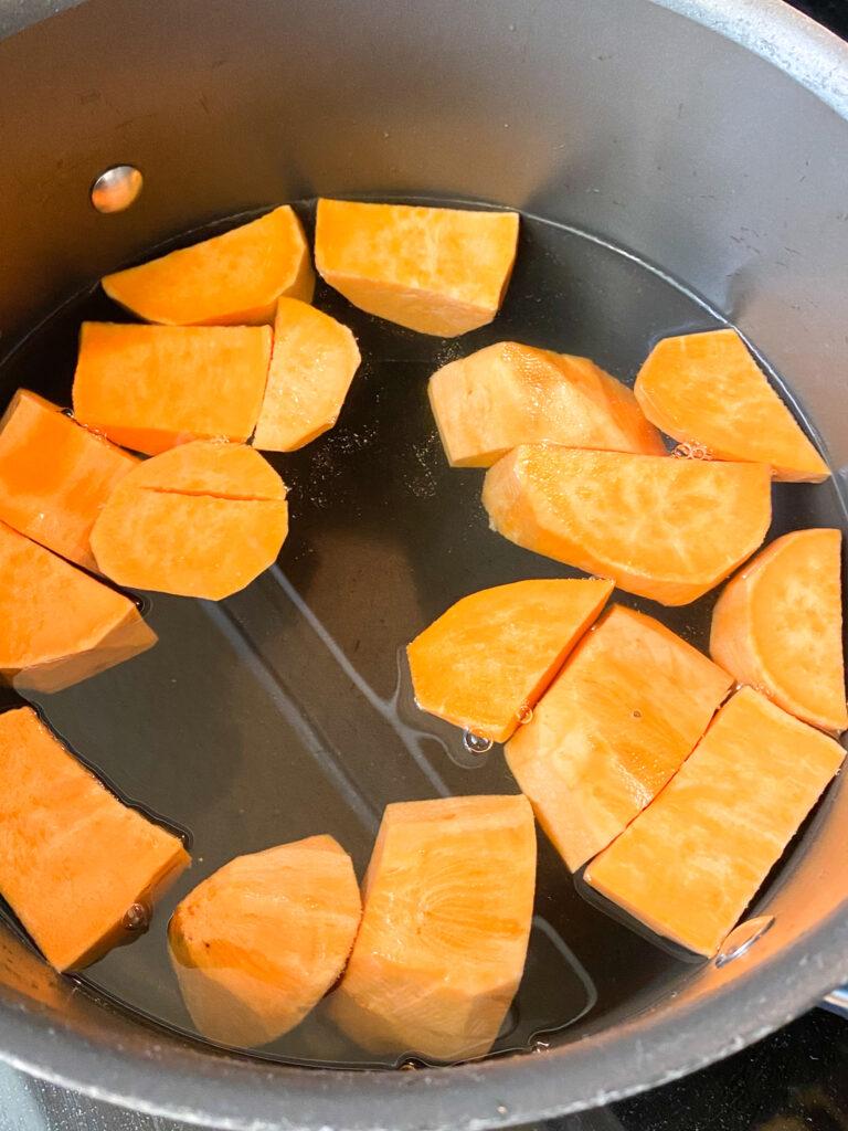 Cubed sweet potatoes in saucepan of water.