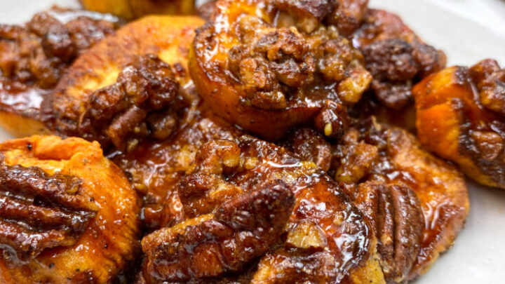 Glazed sweet potatoes with pecans on a white plate.