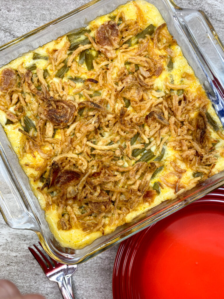 """Baked green bean casserole with cheese in an 8"""" x 8"""" baking dish."""