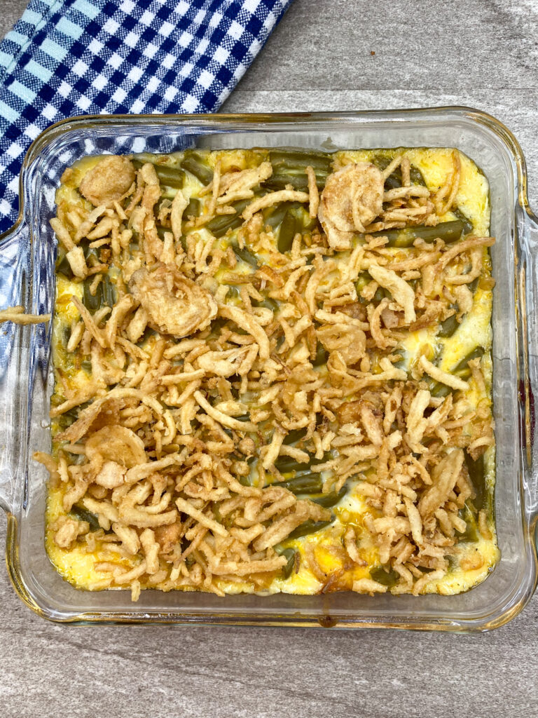 Topping the casserole with fried onions.