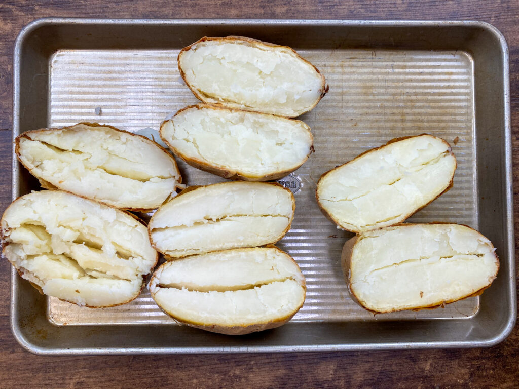 Cooked potatoes sliced and on a cookie sheet.