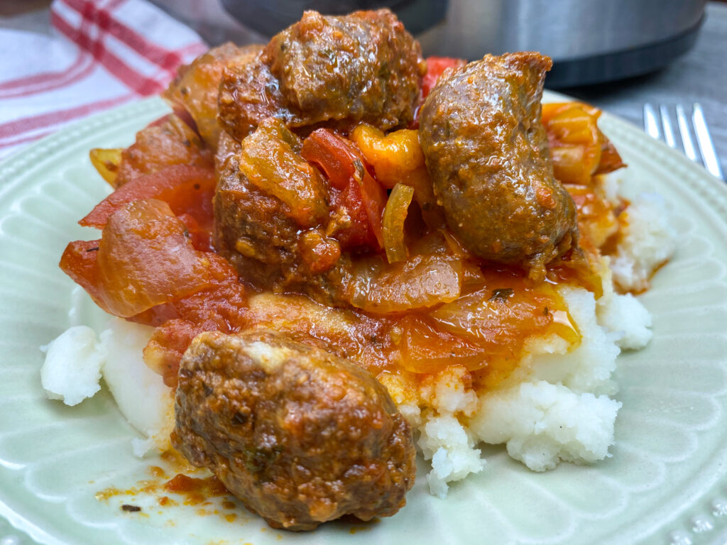 Sausage and peppers on a plate with mashed potatoes