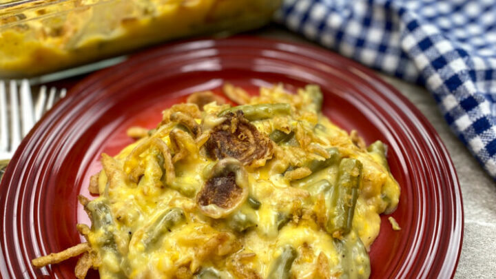 Holiday green bean casserole on a red plate with cheese and onions.