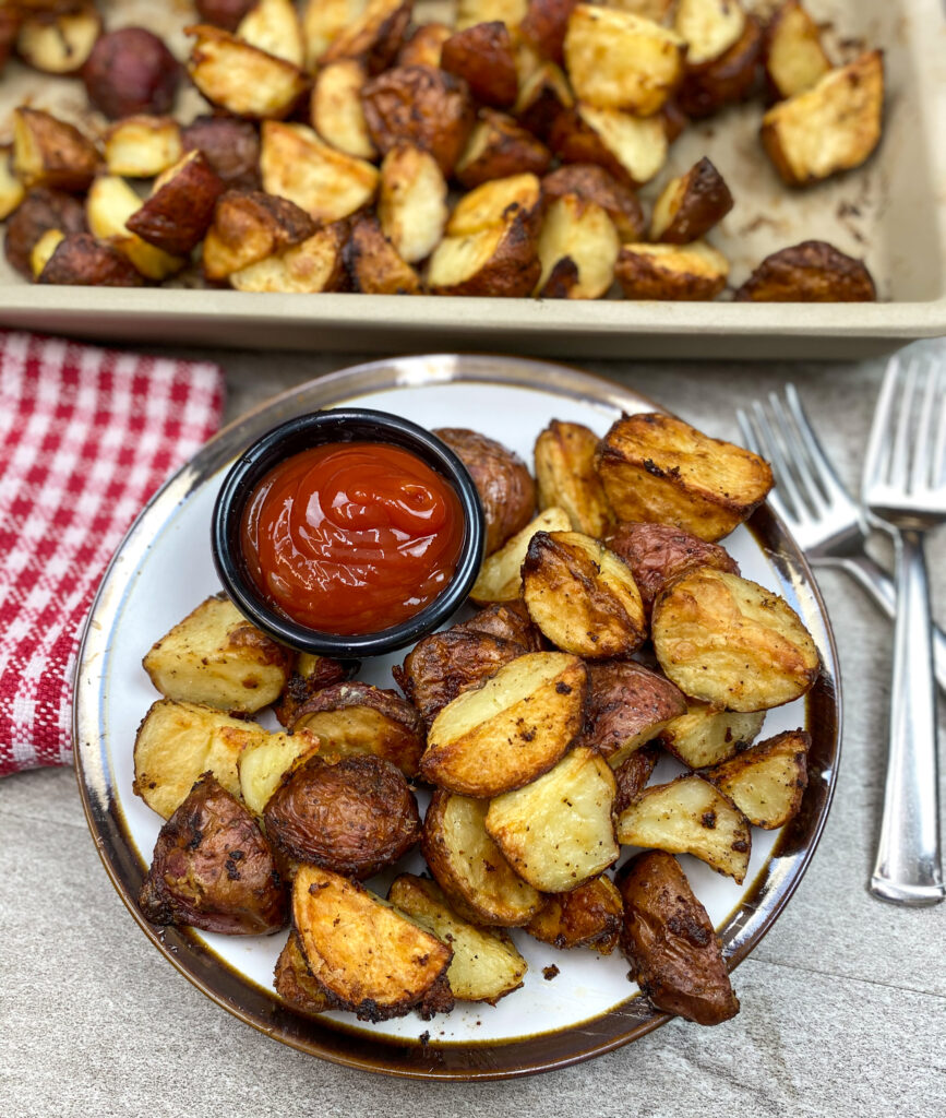 Roasted red potatoes on a white plate with ketchup.