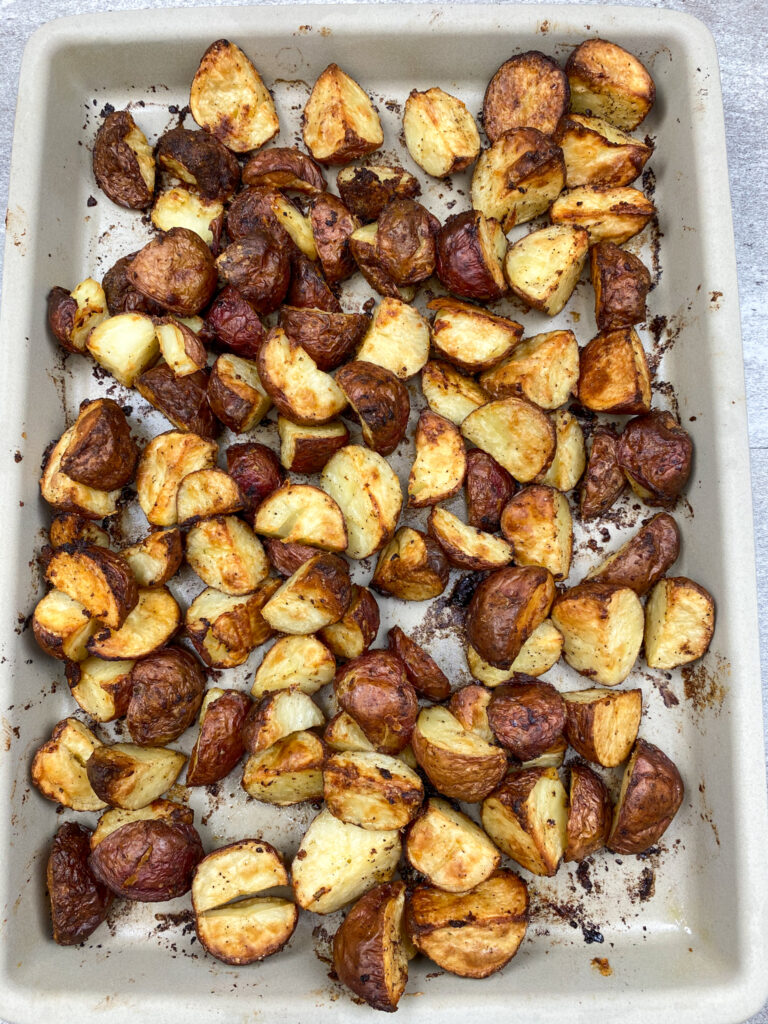 Roasted red potatoes on a baking sheet.