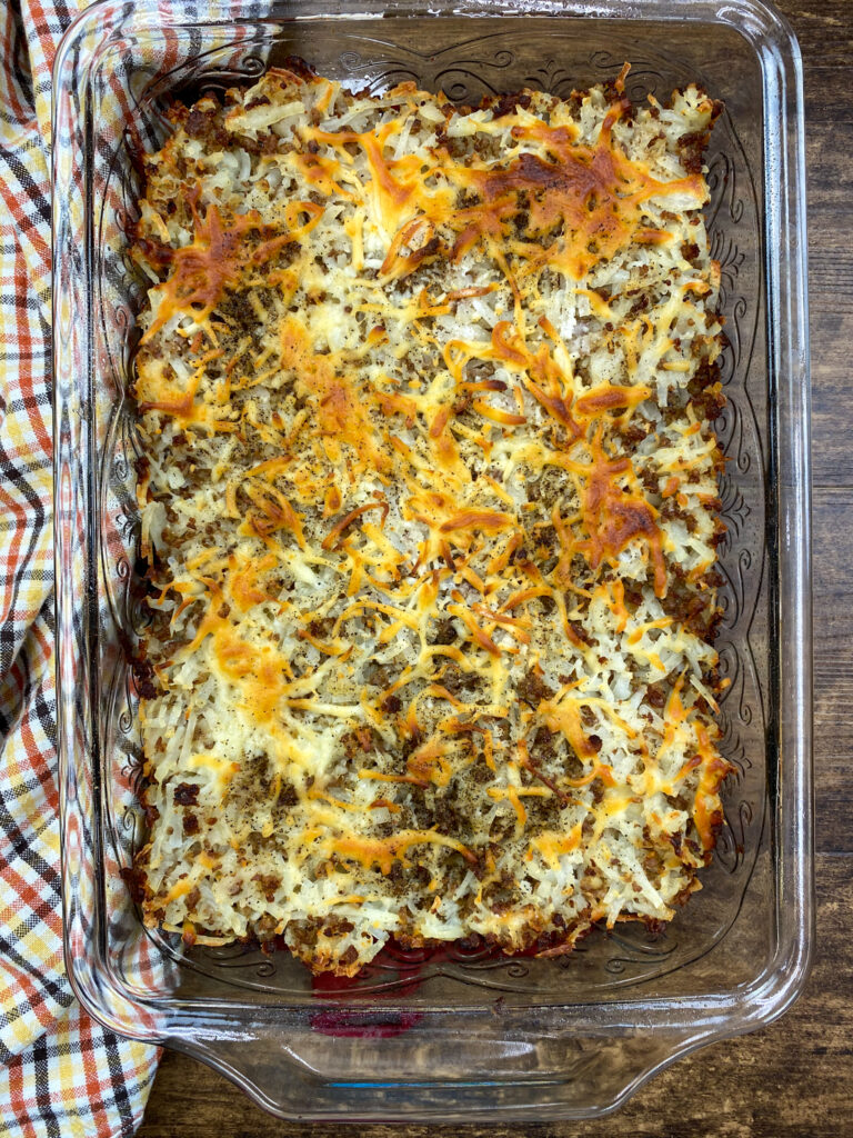 Baked hash browns and sausage with mozzarella cheese in a casserole dish.