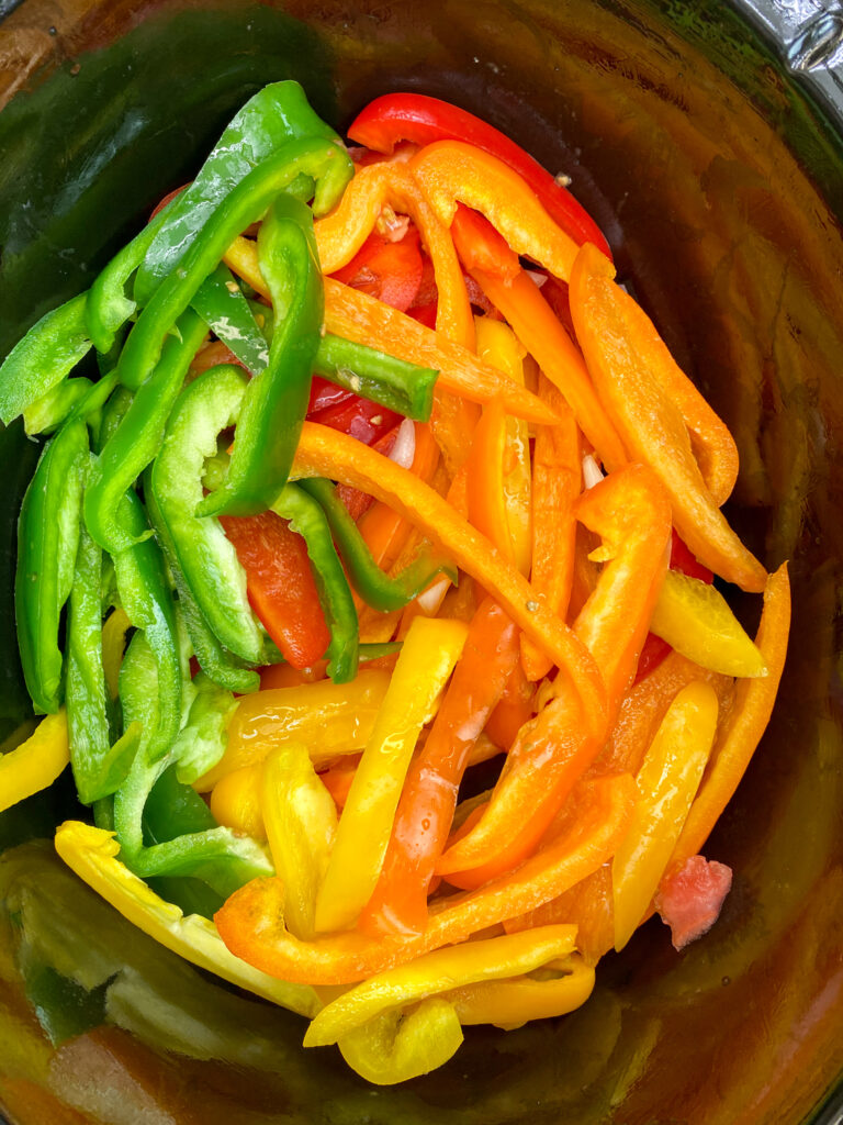 Green, red, orange, and yellow bell peppers sliced in a slow cooker.