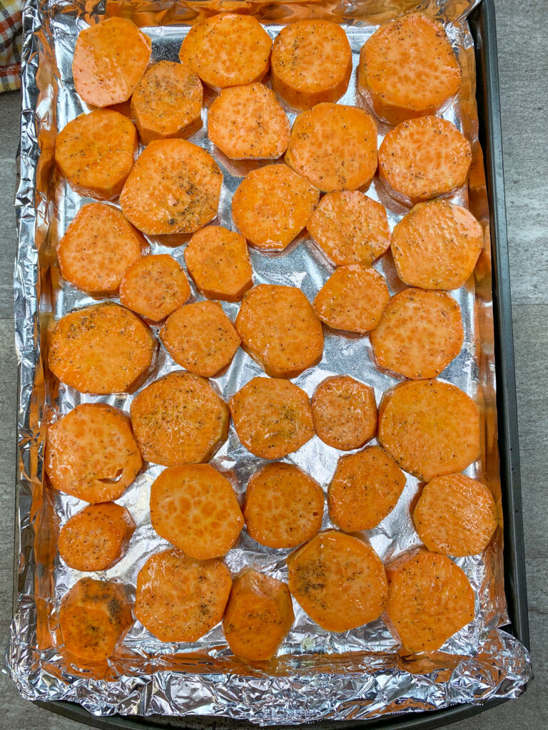 Sweet potatoes on a cookie sheet covered with tin foil.