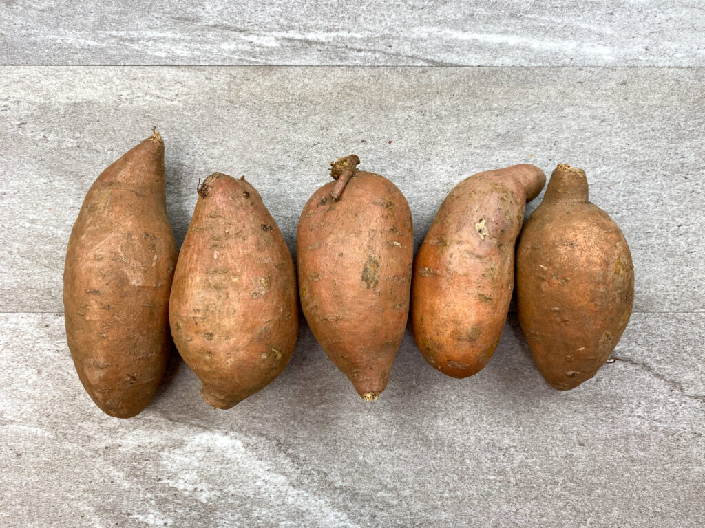 Five sweet potatoes lined up on the counter.