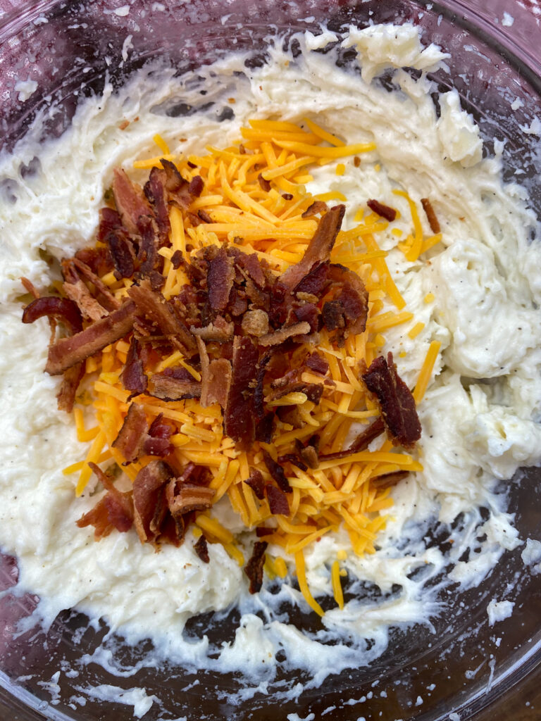 Mashed potatoes with cheese and bacon in a bowl.