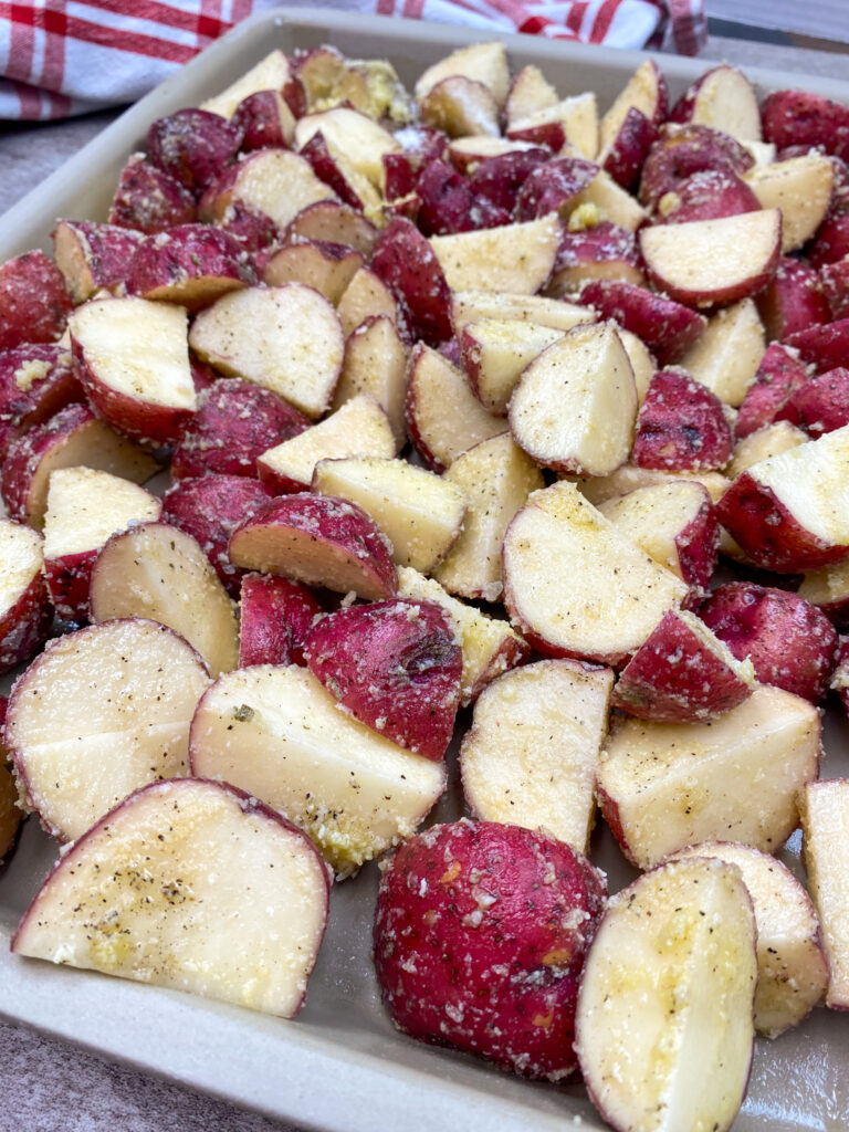 Red potatoes spread out on a baking sheet.