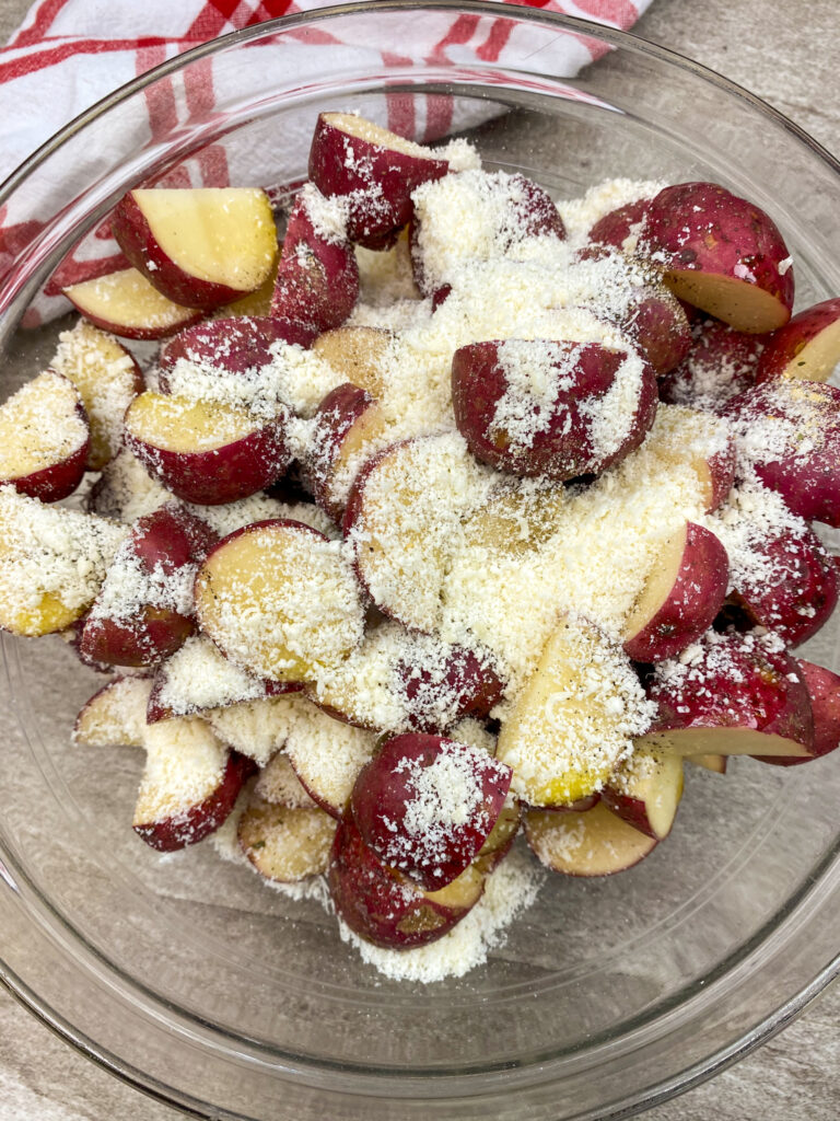 Sliced red potatoes with olive oil, grated parmesan cheese, garlic salt, salt, and pepper in a large glass bowl.