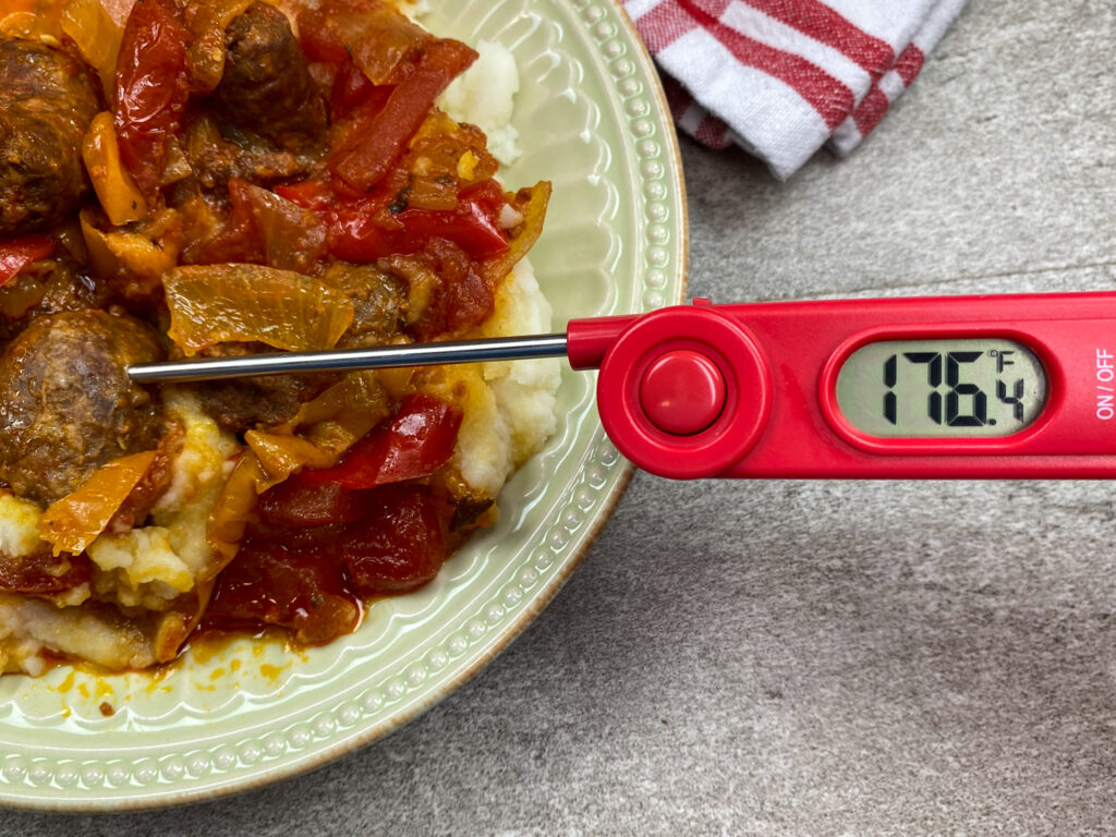 Using a thermometer to check the temperature of the sausage.
