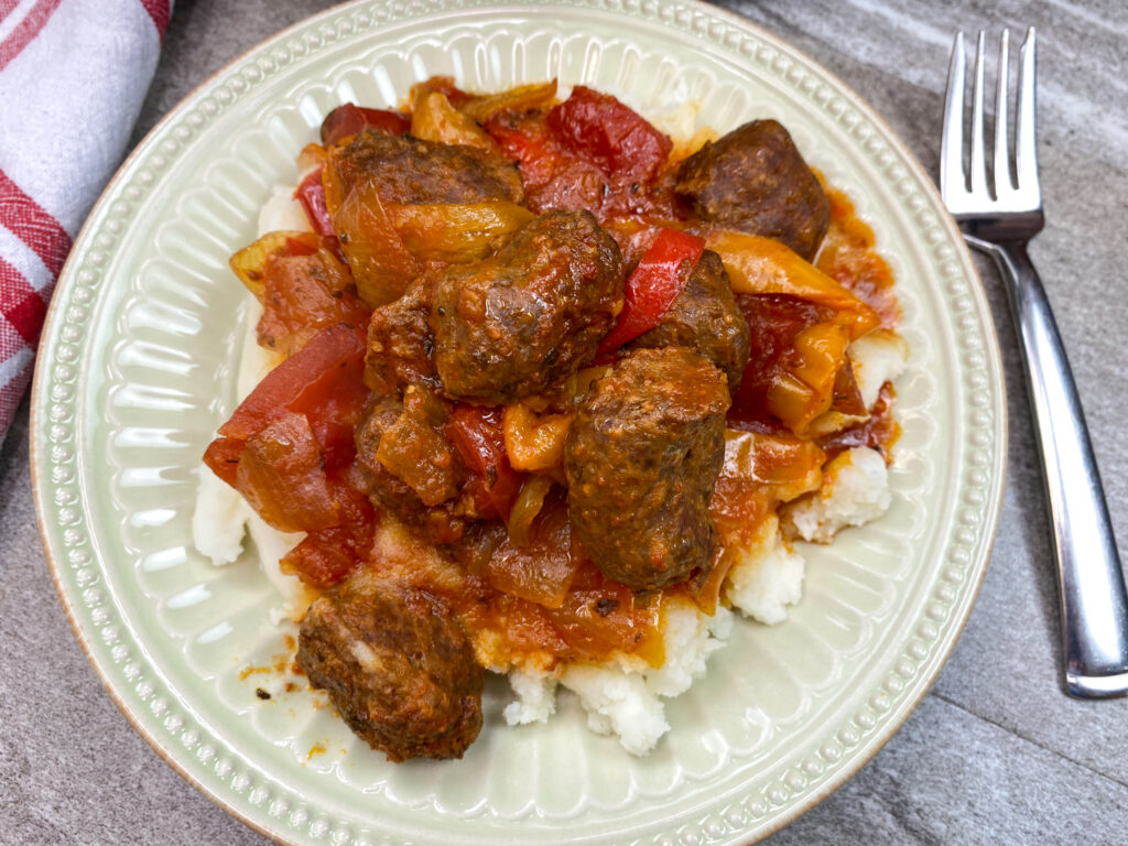 Italian sausage on a plate with peppers and mashed potatoes.