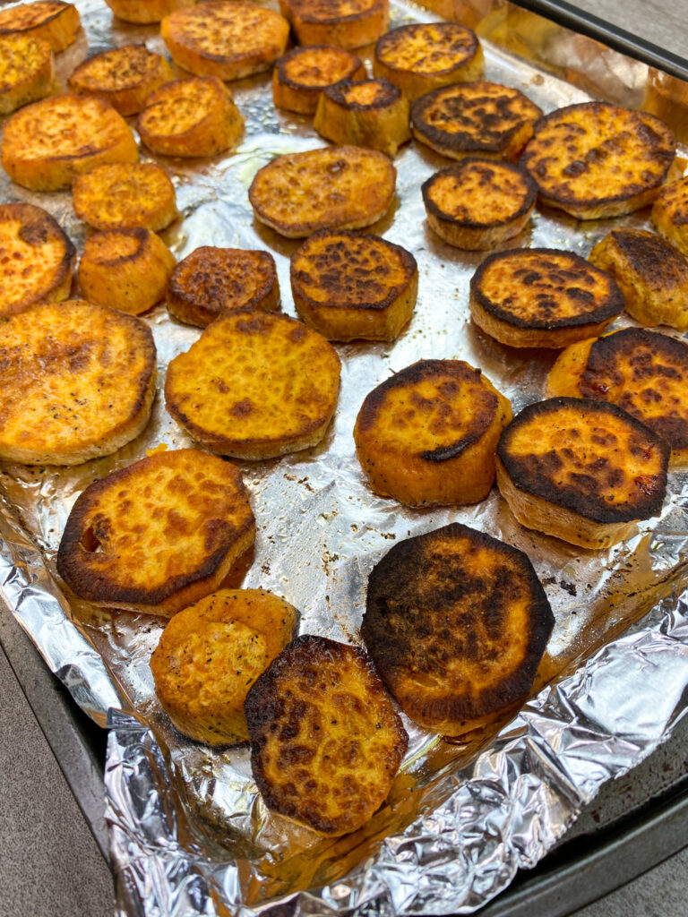 Cooked slices of sweet potato on a cookie sheet covered in tin foil.