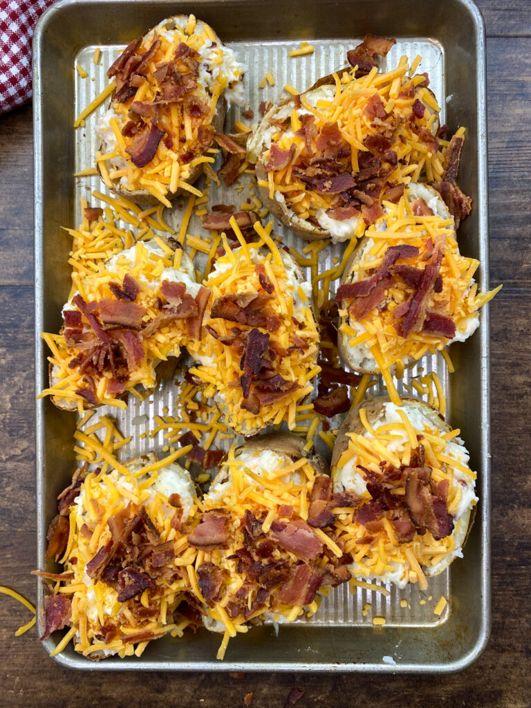 Potato skins topped with shredded cheese and crumbled bacon.