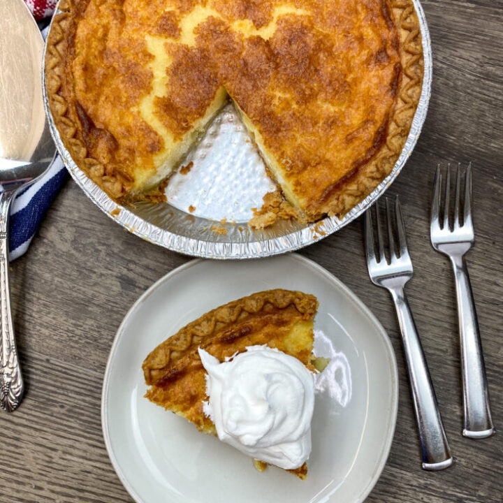 A slice of buttermilk pie on a white plate with whipped topping.