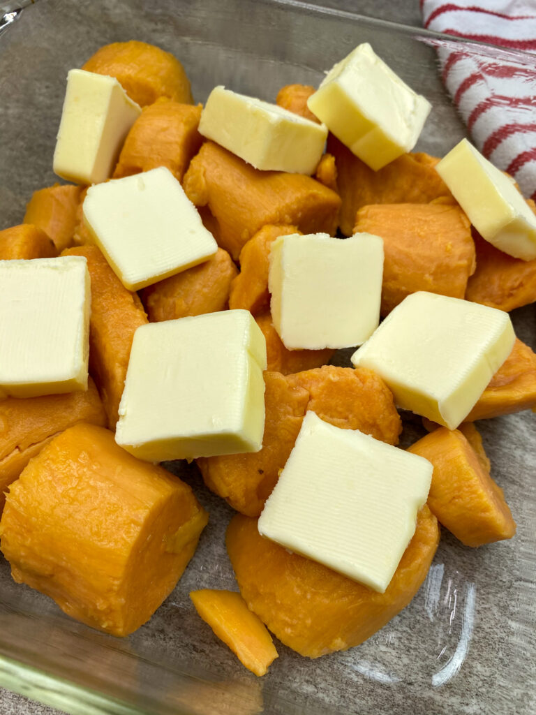 Cubed butter on top of yams in a baking dish.