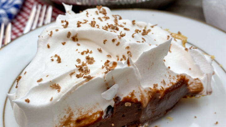 A slice of chocolate cream pie on a white plate.