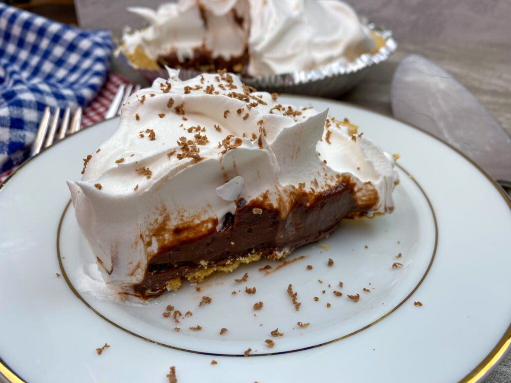 Chocolate cream pie on a white plate.
