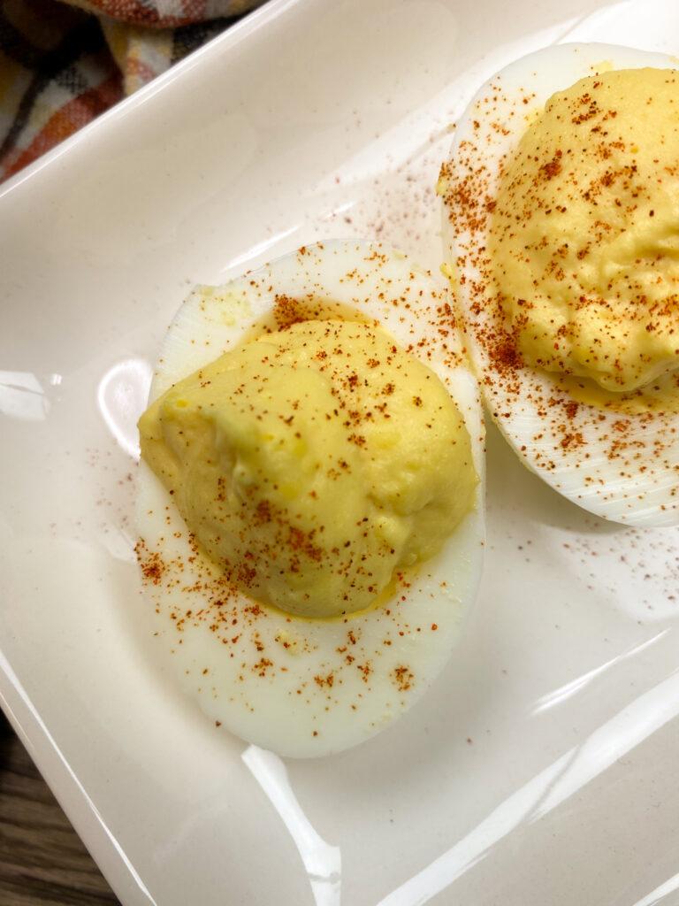 Deviled eggs on a white platter.