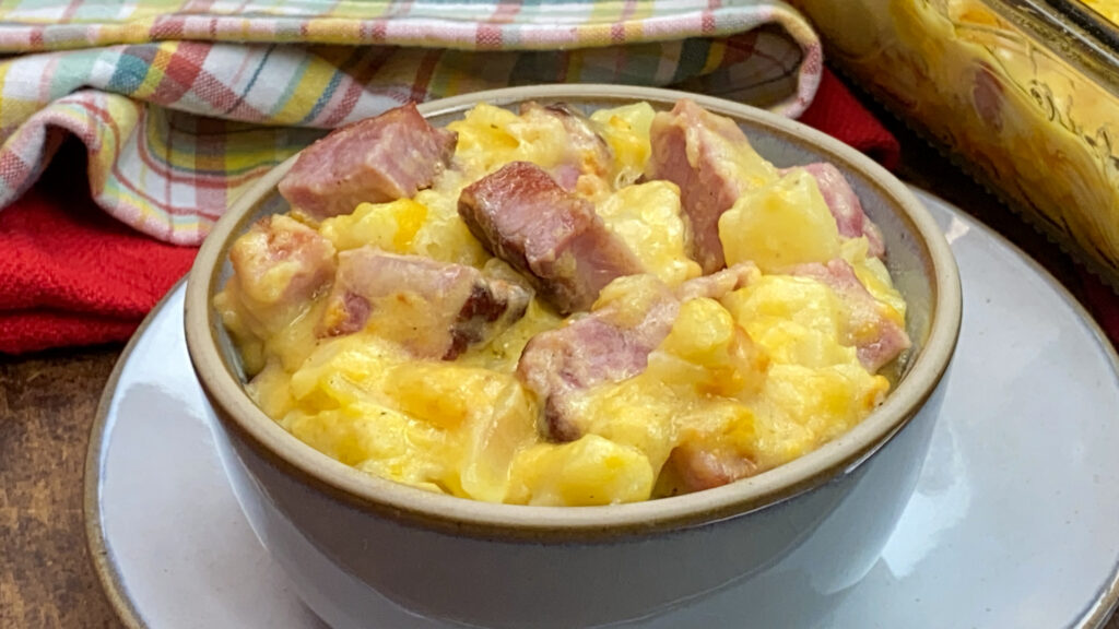 Cheesy ham and potatoes in a small bowl.