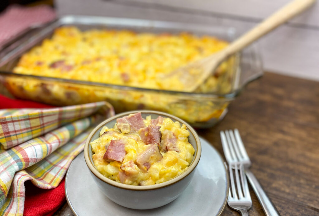 Ham and potatoes, with cheese, in a bowl and baking dish.