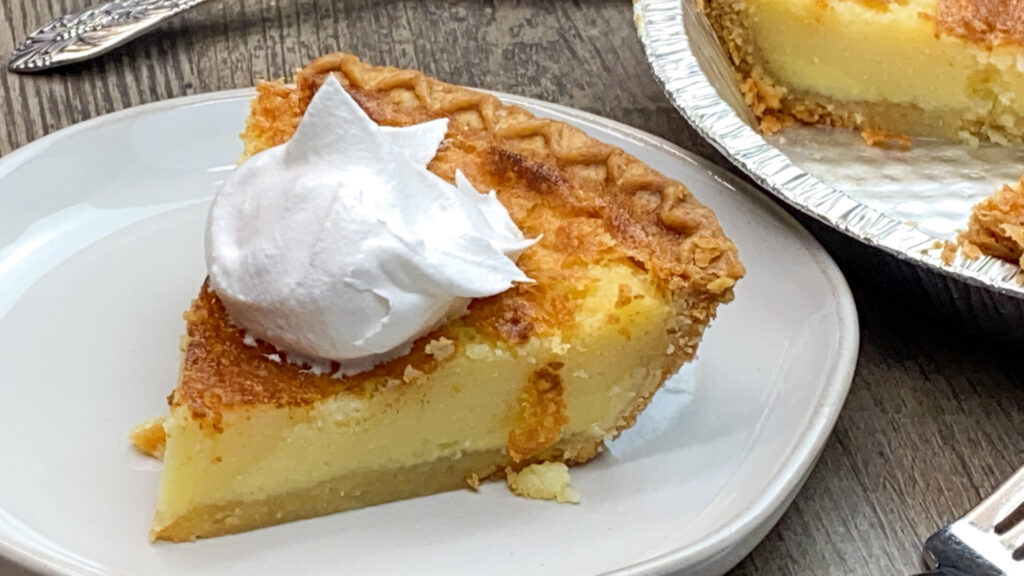 A slice of buttermilk pie on a plate with whipped topping on top